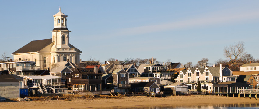 A cluster of homes and businesses along Commercial Street in Provincettown, Massachusetts back up to the town beach.  The town library (left) was a recent renovation and conversion from a   church.